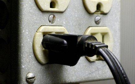 An image of a black powerplug plugged into an outlet with four ports.