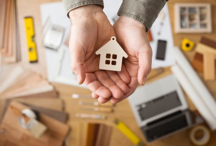 cupped hands holding small icon of a house