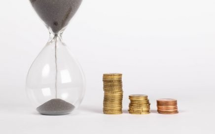 Hourglass with coins, estimate time and cost for copyediting