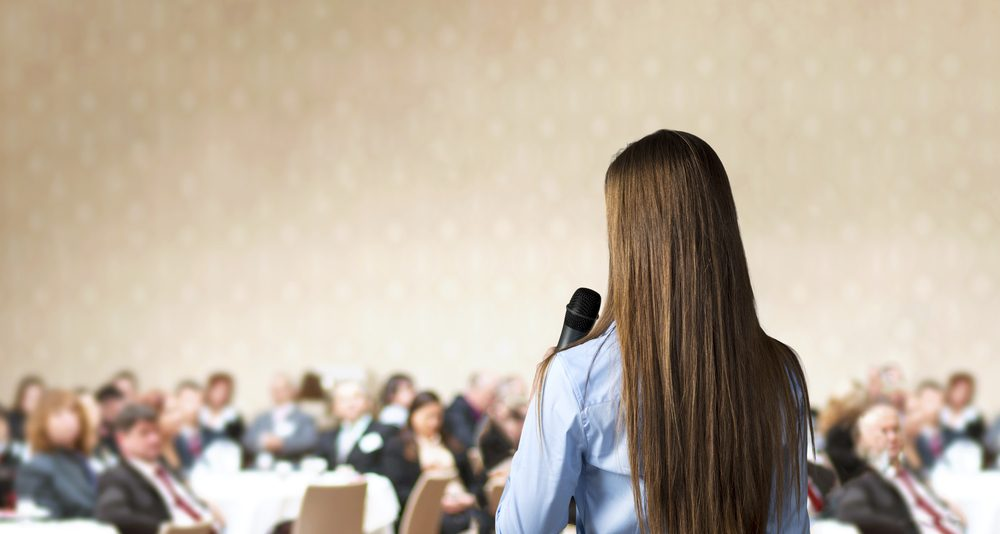 Image: woman holding microphone and speaking to a crowded room