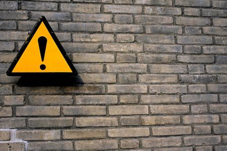 Image: brick wall with sign containing exclamation point