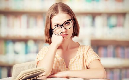 Image: woman in library, looking fed up with books