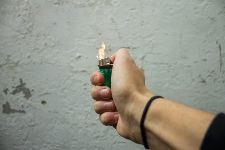 Image: woman's hand sparking a disposable lighter