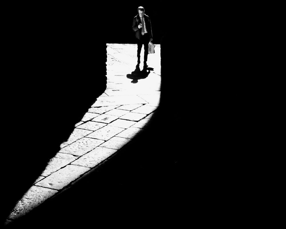 Image: man standing in comma-shaped beam of light