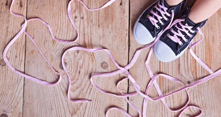 Image: a child's shoes with laces that are too long and tangled
