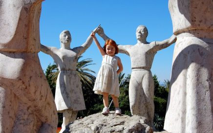 Image: young re-headed girl standing amid a ring of figurative statues