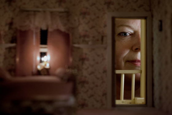 Image: inside of a dollhouse, with a woman looking in through the window