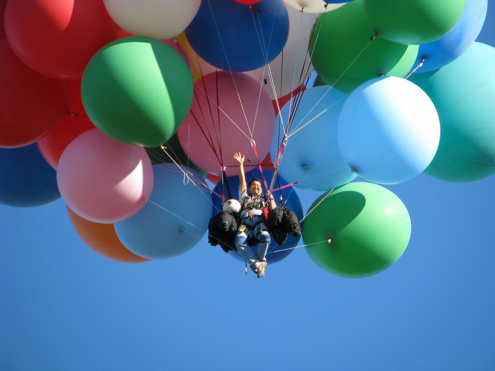 Image: man in the air, held aloft by dozens of balloons