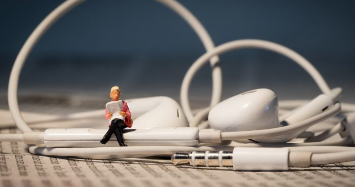 Image: miniature figure sitting atop a pair of wired earbuds, reading aloud
