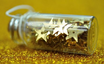 Image: a small bottle full of gold metal stars