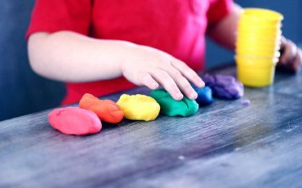 Image: a young boy preparing to sculpt shapes from clay