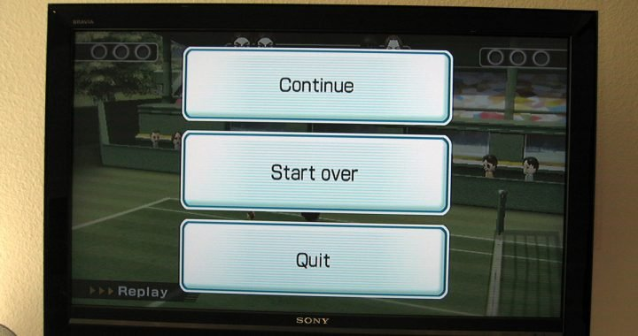Image: television displaying a video game menu of three buttons labeled Continue, Start Over, and Quit