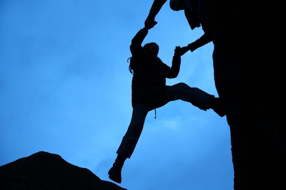 Image: silhouette of one hiker helping another up the cliff face