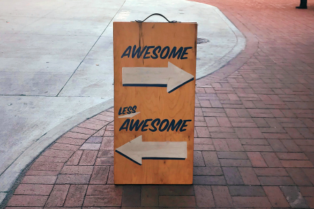 Image: wooden sign on urban sidewalk, painted with two arrows; the arrow pointing right is labeled 'Awesome' and the arrow pointing left is labeled 'Less Awesome'
