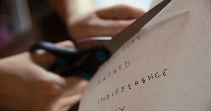 "Image: person using scissors to cut a piece of paper on which are written the words ""hatred,"" ""indifference,"" and ""envy"""