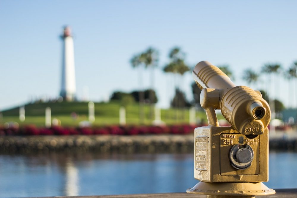 Image: coin-operated viewfinder positioned across the water from a lighthouse