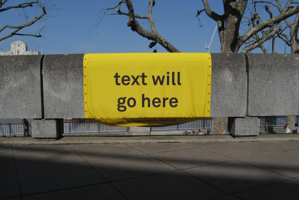 """Image: a sign printed with the words """"text will go here,"""" draped over a wall"""