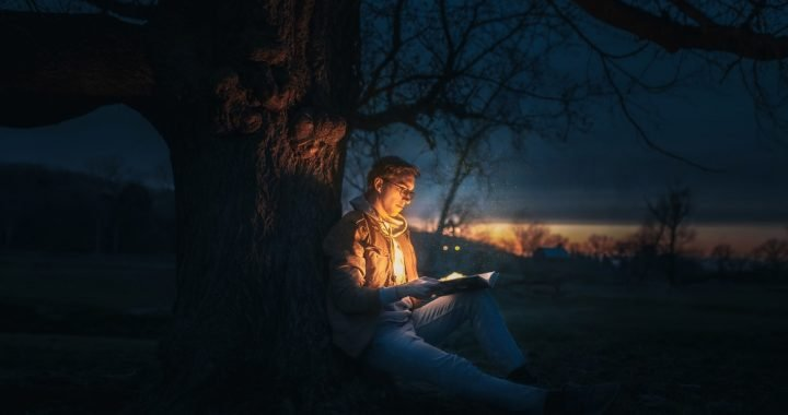 Image: young man sitting against a tree in the evening, reading a book from which emanates a glow