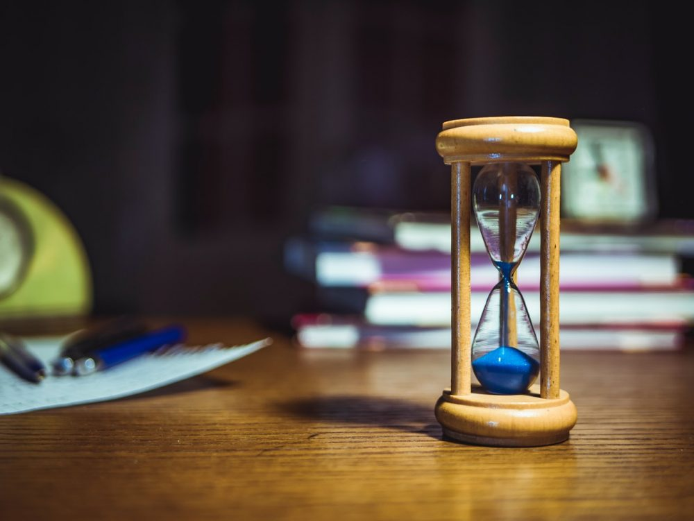 Image: small hourglass on a table with books, pens, and paper in the background.