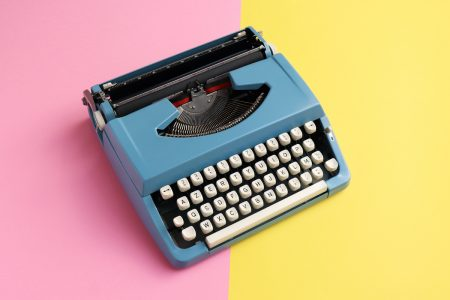 Image: vintage blue typewriter on a background that's half pink and half yellow