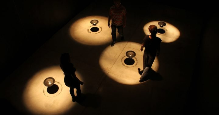 Image: art installation of a dark room containing four audio speakers suspended in mid-air and lit by spotlights, with people walking through the space.