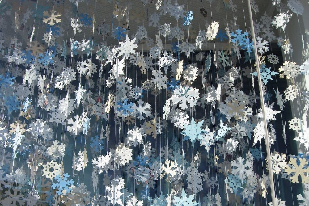 Image: hundreds of paper snowflakes hanging by threads from a ceiling