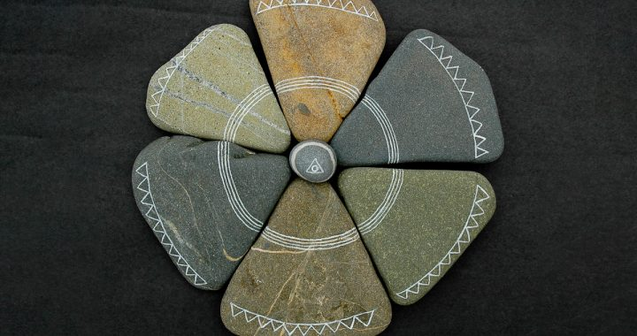 Image: six flat triangular stones arranged in a circle, with a small round stone at their center
