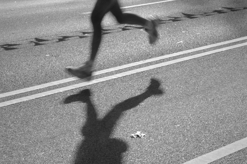 Image: legs and shadow of a lone runner in the middle of a city street