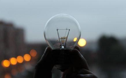 Image: hand holding an unlit lightbulb