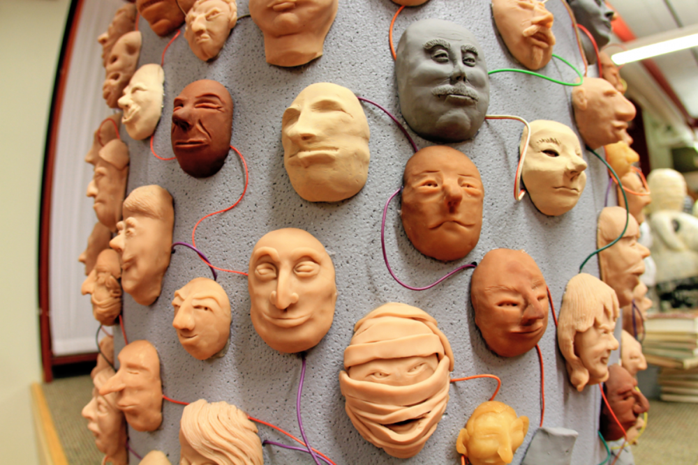 Image: sculpture of many faces attached to a column, all connected to one another by colorful wires.
