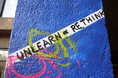 """Image: urban wall with graffiti reading """"Unlearn and rethink."""""""