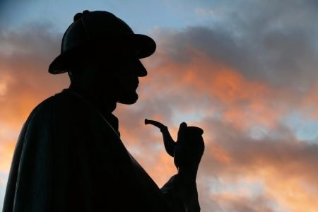 Image: Sherlock Holmes statue silhouetted against a colorful evening sky.