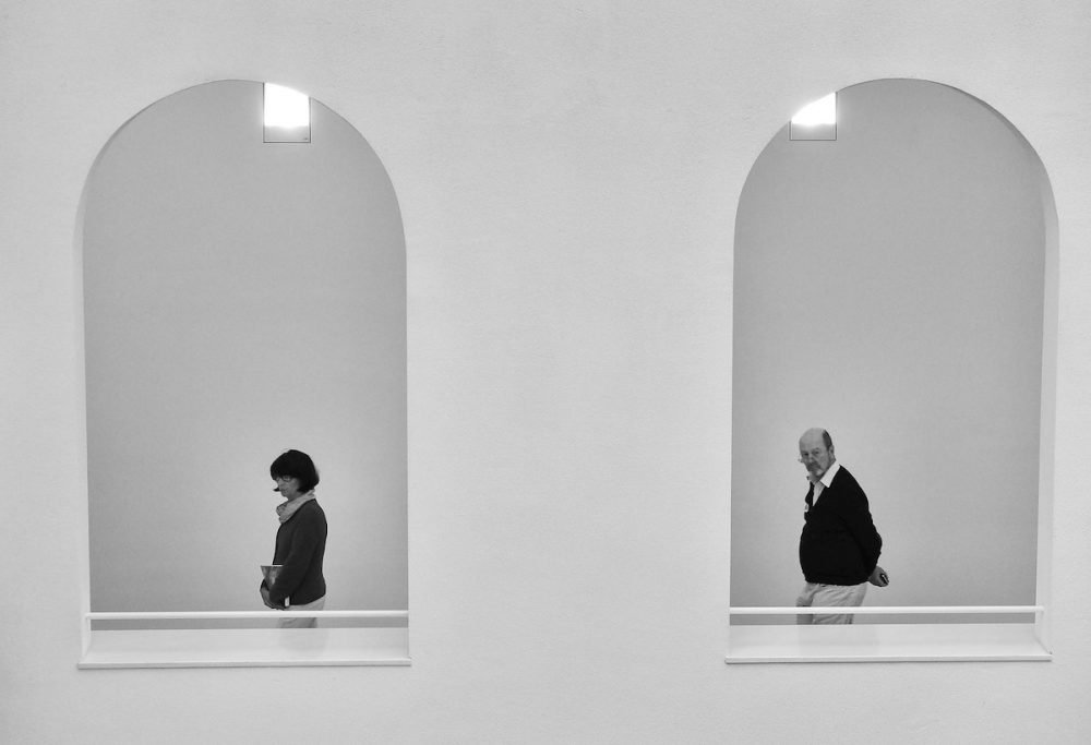 Image: two opens windows in a wall, one frames a woman walking past and the other frames a man walking behind her.