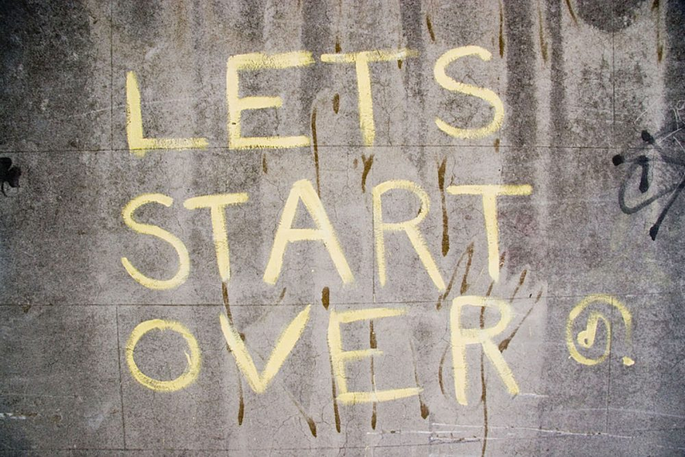 """Image: urban wall with graffiti reading """"Let's start over."""""""
