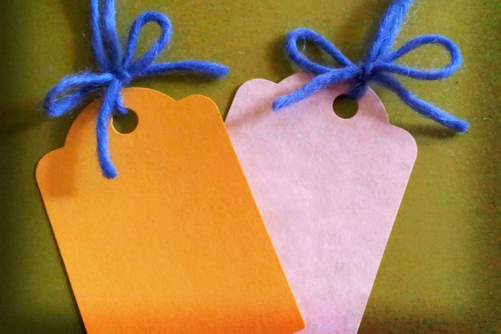 Image: blank gift tags tied to colorful yarn